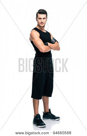 Full length portrait of a fitness man standing with arms folded isolated on a white background. Looking at camera