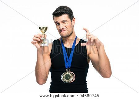 Sports man showing small winners cup isolated on a white background. Looking camera