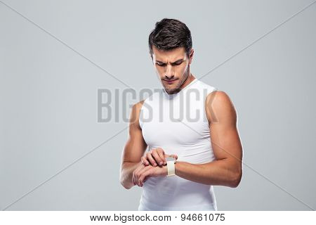 Handsome sports man using smart watch over gray background
