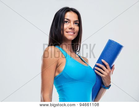 Smiling sports woman holding yoga mat over gray background