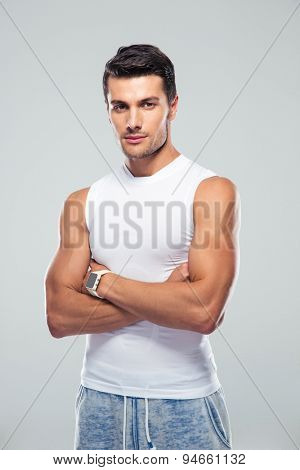 Handsome young man standing with arms folded over gray background over gray background