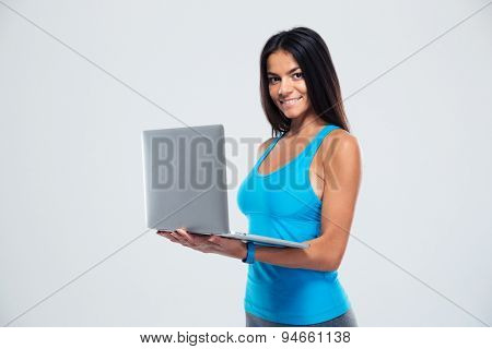 Happy fitness woman using laptop over gray background. Looking at camera