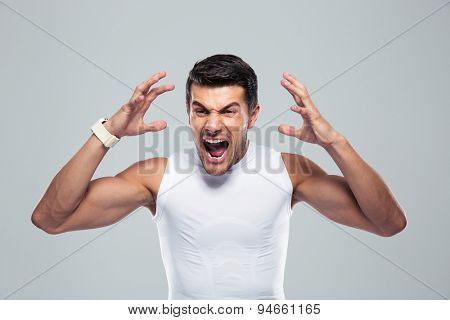 Portrait of angry fitness man shouting over gray background