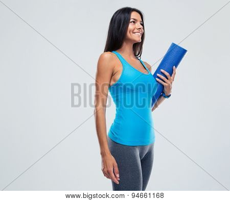 Cheerful sports woman holding yoga mat over gray background. Looking up