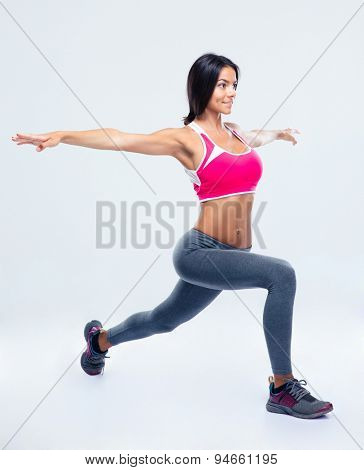 Full length portrait of a fitness woman stretching over gray background