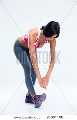 Full length portrait of a sporty woman stretching over gray background