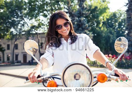 Young happy italian woman riding a scooter in the city