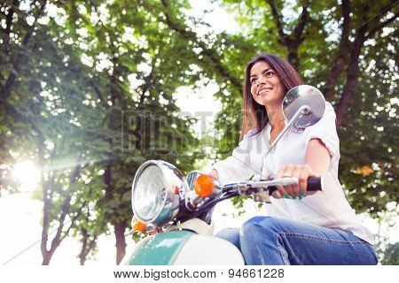 Young cheerful woman riding vintage scooter