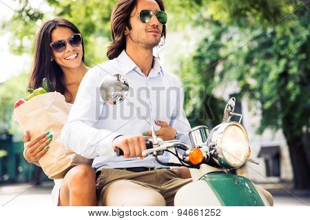 Happy young couple driving scooter while woman holding bag full of groceries. Summer time.