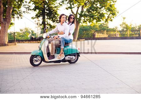 Sideview of a trendy couple riding a scooter in the morning