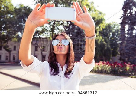 Glamorous girl making a selfie with her smartphone outdoors