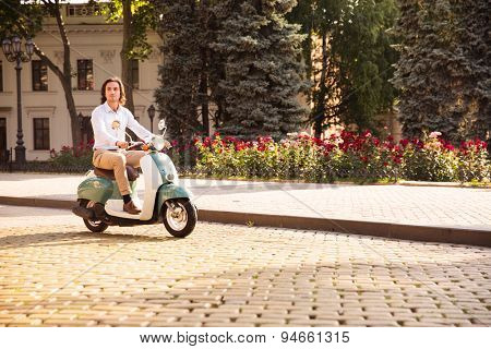 Confident young man riding a scooter through town streets in the morning