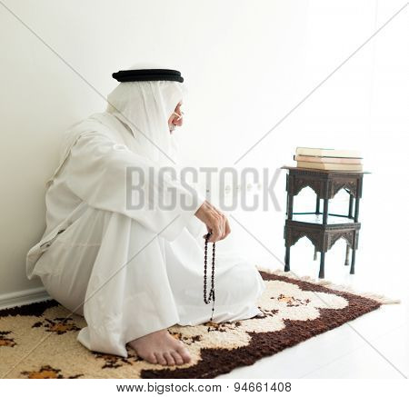 Arabic aged man sitting on ground using traditional beads