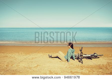Woman Resting Near A Bicycle On Beach