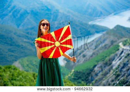 Woman with macedonian flag on the top of mountain