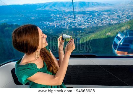Woman in cable car with cityscape view