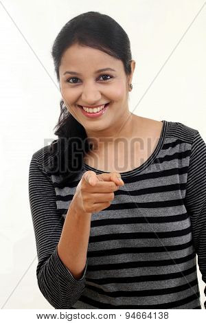 Young Woman Pointing At A Product While Looking At The Camera