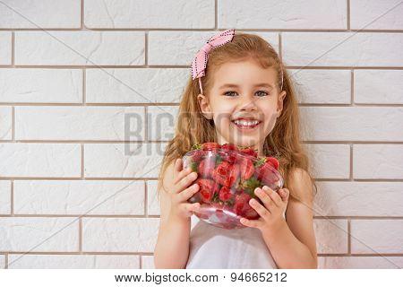 beauty child enjoying a fresh strawberry
