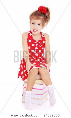 girl in a red dress with polka dots sitting on the books