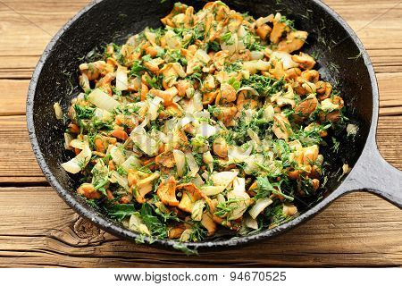 Fried Chanterelle Mushrooms With Greens In Black Cast Iron Pan
