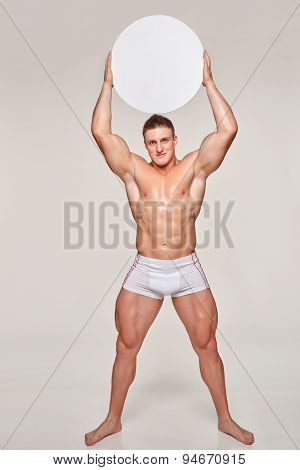 Muscular man uplifting blank circle copy space