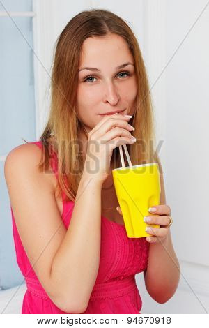 girl in a pink dress with yellow glass hand at home