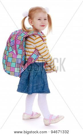 Adorable little girl in pigtails with a big knapsack on his back