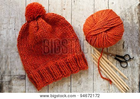 wool orange hat, knitting needles and yarn on wooden background