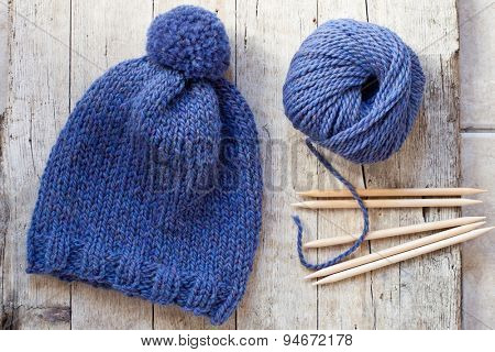 wool blue hat, knitting needles and yarn on wooden background