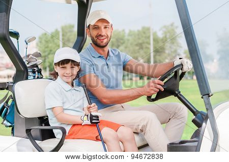 Father And Son In Golf Cart.