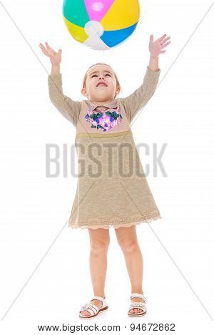 Little girl in dress throws up the ball
