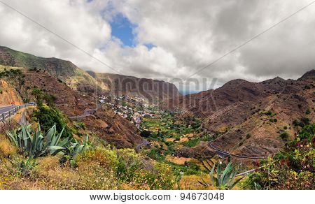 scenic landscape of mountain valley with blue sky, white clouds and colorful houses (Tenerife, Canary islands, Spain)