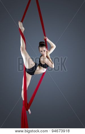 Flexible female gymnast performing aerial exercise