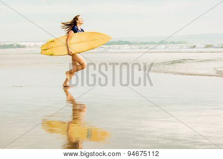 Beautiful sexy surfer girl on the beach at sunset running into ocean, yellow surfboard in her hands.
