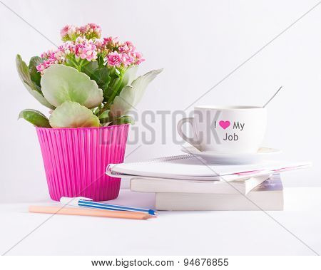 Workplace with flower books and a coffee cup with text 'I love my job