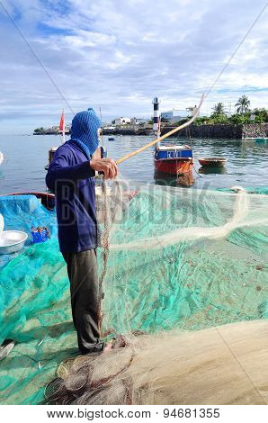 Quang Ngai, Vietnam - July 31, 2012: An Old Fisherman Is Removing Anchovies Fish From His Fishing Ne