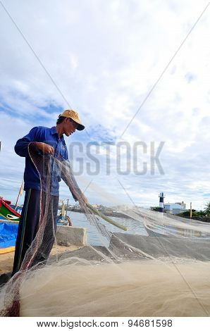 Quang Ngai, Vietnam - July 31, 2012: A Fisherman Is Removing Anchovies Fish From His Fishing Net To