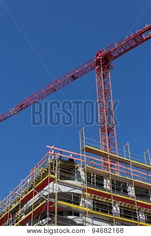 building construction site - facade with scaffolding and crane