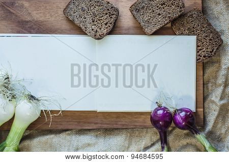 Frame Made Of Onions And Black Bread Around Book