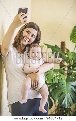 Woman With A Baby Doing A Selfie