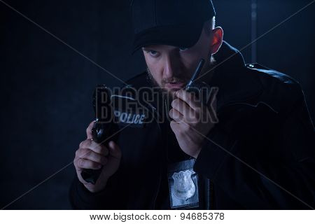 Policeman Holding Radio And Gun