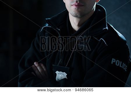 Policeman Standing With Crossed Arms