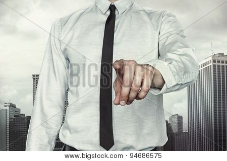Businessman pointing finger on cityscape background