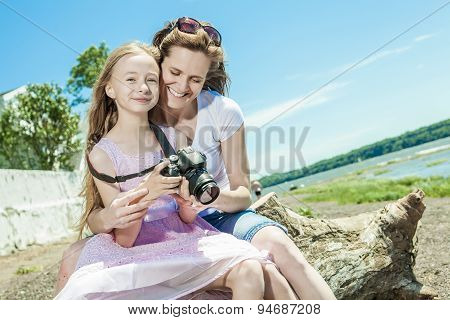 Cheerful mother taking picture of her cute little daughter.