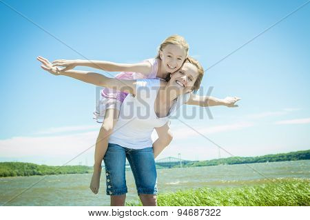 Young girl hugging her mother piggyback style