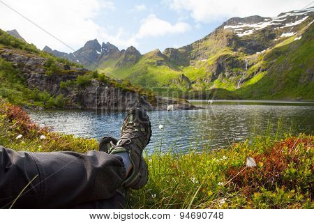 Hiker resting near mountain lake