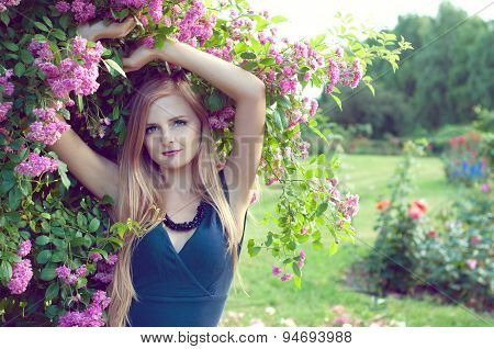 Beutiful blonde woman in the rosary garden
