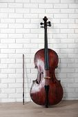 stock photo of cello  - Cello on bricks wall background - JPG