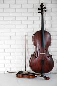 foto of cello  - Cello and violin on bricks wall background - JPG