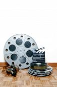 picture of mm  - 35 mm cinema movie roll and reels with clapper and filmstrip on wooden floor and white wall background - JPG